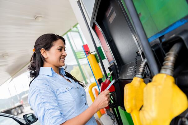 Woman using a gas card at the pump