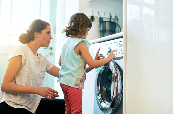 Mom showing daughter how to use dryer