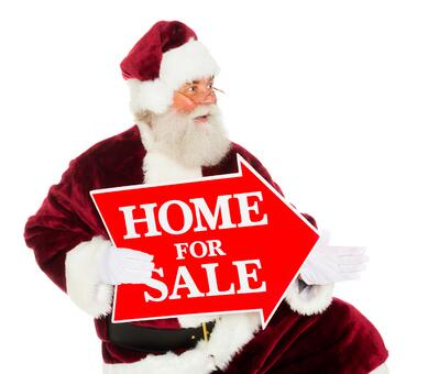 Santa holding a home for sale sign