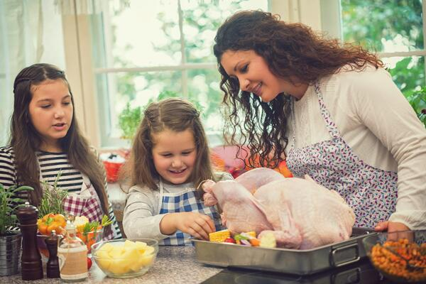 Mom and young daughters cooking Thanksgiving turkey