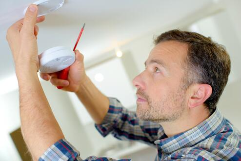 man installs a smoke detector in home