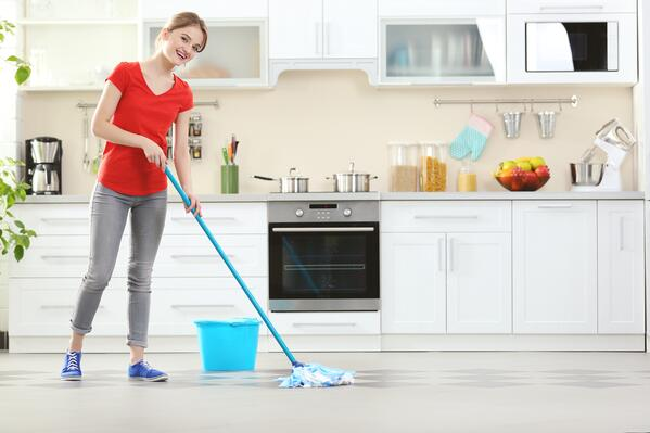 Happy woman mopping the kitchen floor